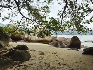 O lado direito da praia possui pedras de diferentes tamanhos e formatos